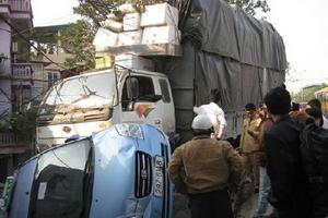 Taxi bị lật ngửa do xe tải đâm.