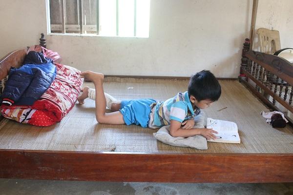 Nằm liệt giường đã lâu, cháu Trần Thái Phú nhớ trường lớp, thường mang sách vở ra ôn bài