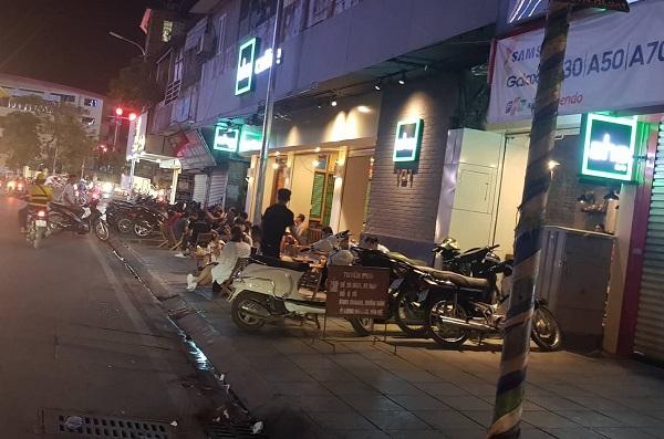 Aha tại Tôn Thất Tùng, xe cộ và khách hàng ngồi tràn ra vỉa hè, mặc dù ngay cạnh có biển báo cấm.