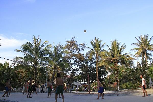 Ngoài giờ huấn luyện, tăng gia, cán bộ, chiến sĩ ở Trường Sa thường chơi bóng chuyền. Có những quy tắc rất riêng ở Trường Sa, chẳng hạn đội thua phải vừa ngậm lá vừa đánh bóng. Trong ảnh, cán bộ, chiến sĩ đảo Nam Yết chơi bóng chuyền. Ảnh: Trường Phong
