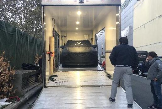 Chiếc xe được phủ bạt đen kín in hình logo VinFast trong chiếc xe container.
