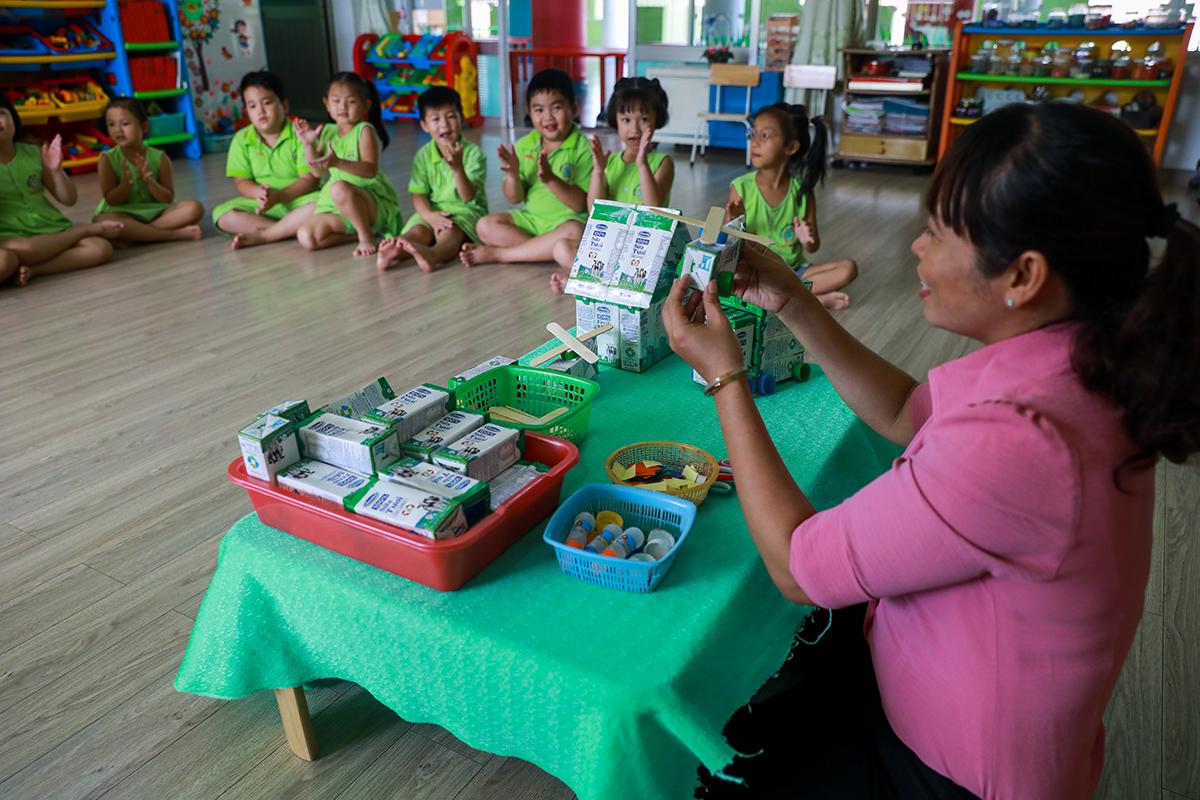 Giáo viên trường Mầm non Thị trấn Củ Chi 2 (TP HCM) hướng dẫn các em làm đồ chơi từ vỏ hộp sữa đã uống. Ảnh: Quỳnh Trần.