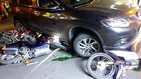 'Xế hộp' cuốn hàng loạt xe máy vào gầm, 4 người bị thương