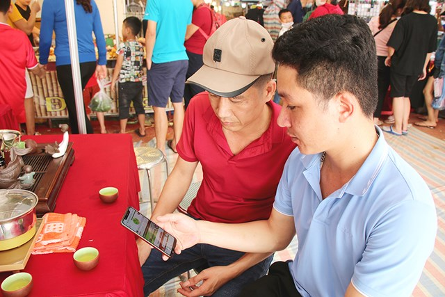 Anh Hà Văn Chinh (áo xanh) – Phó Giám đốc HTX sản xuất chè an toàn Long Cốc giới thiệu cho khách hàng về địa chỉ trang web của công ty - Ảnh: Báo Phú Thọ